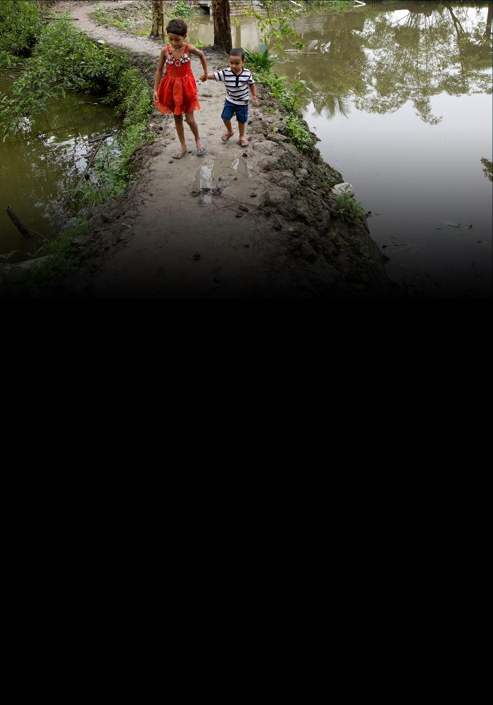 Children in Bangladesh walking on embankment with water on both sides